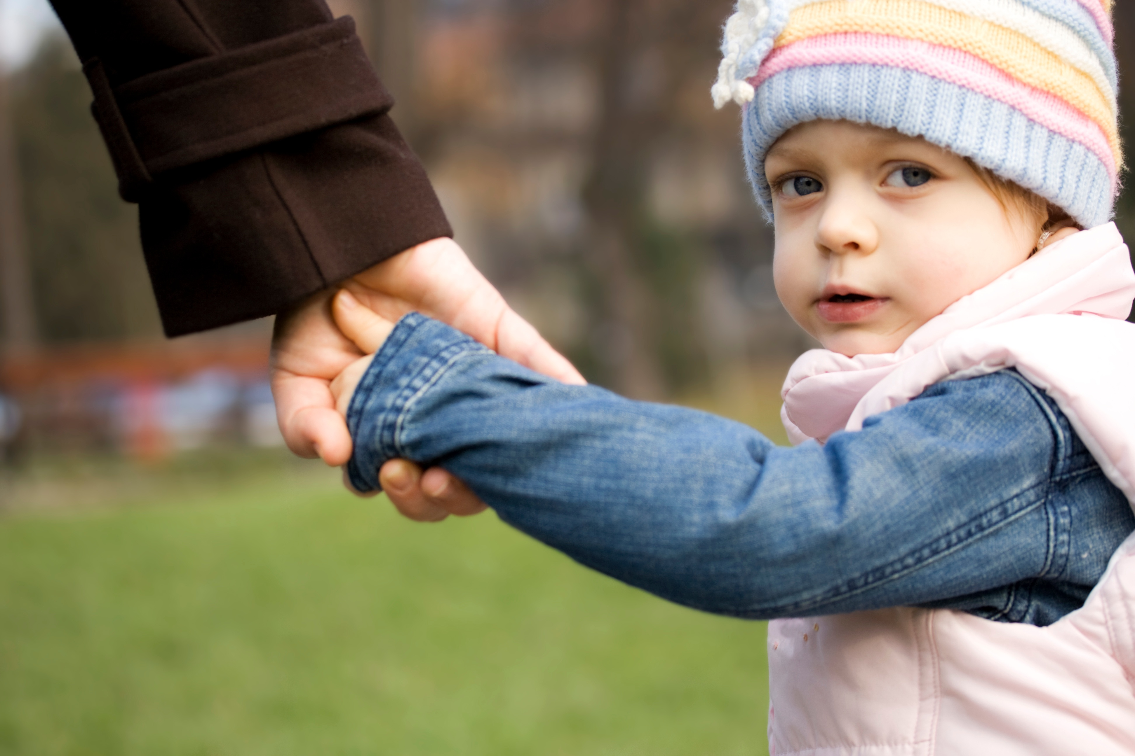 Child holding father's hand after child custody dispute