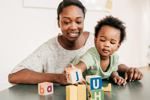 Mother teaches her son how to spell with blocks