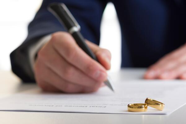 Two rings sitting on top of divorce papers that man is signing