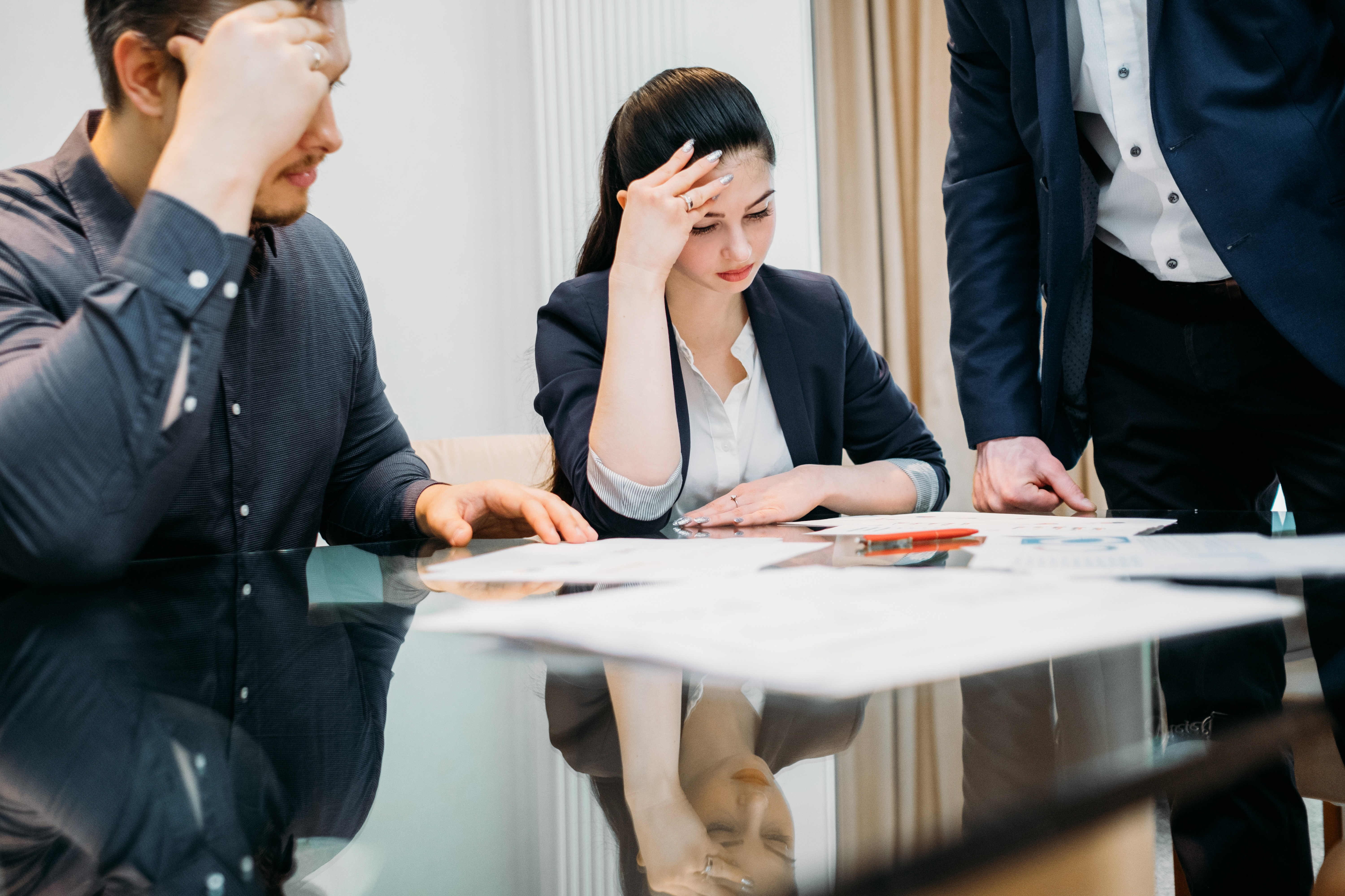 Man and woman working with a lawyer to sign a divorce decree into motion