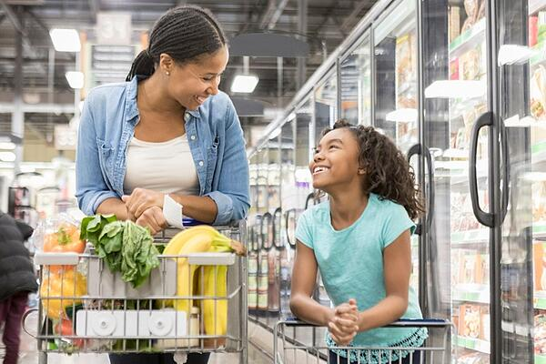 Mom and daughter smiling at grocery store after meeting with child custody lawyer