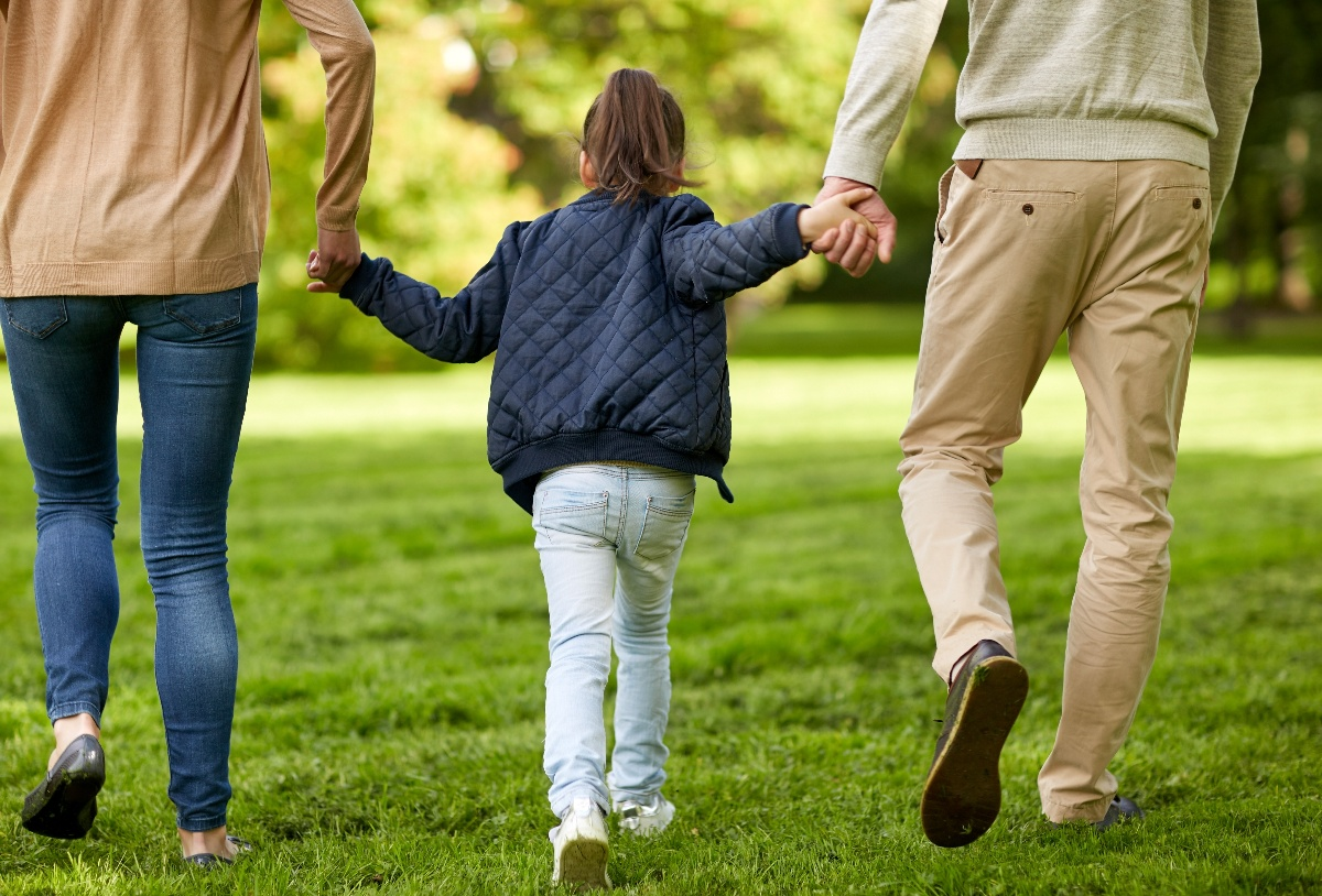 Adopted older child happily walking in a park with her adoptive parents