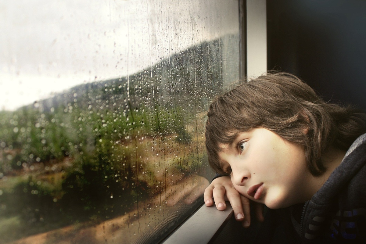 Abandoned sad child looking out window